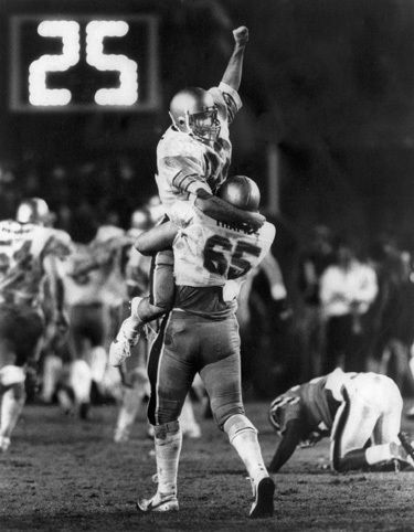 Doug Flutie exults after throwing his last-second TD pass to Gerard Phelan that gave BC a 47-45 win over Miami in 1984, one of the most memorable moments in University history.