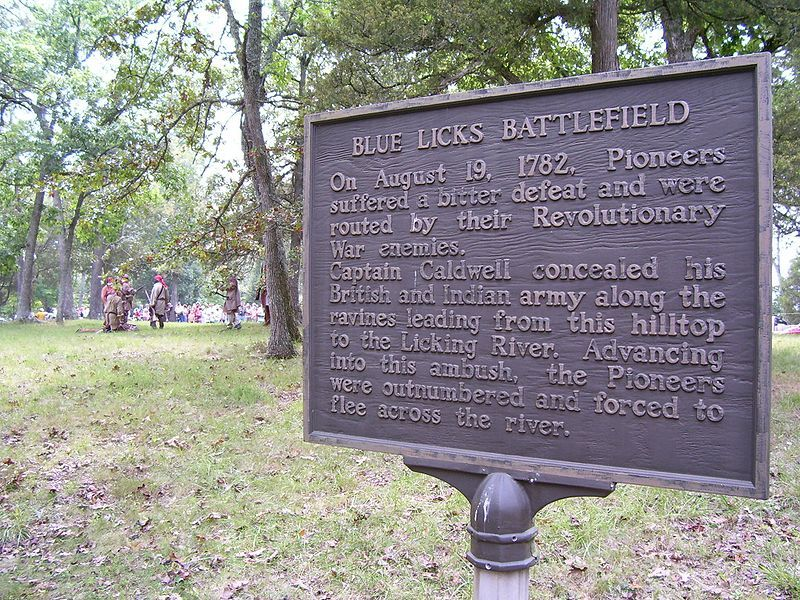 Historical marker at the battle site. In the background, a crowd watches a reenactment of the battle.