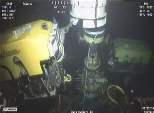 In this image taken from video at 18:15 CDT, a deep-sea robot lowers a new containment cap over the broken wellhead at the site of the Deepwater Horizon oil spill in the Gulf of Mexico, July 12, 2010.