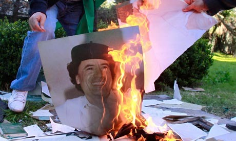 Employees of the Libyan embassy in Buenos Aires burn a portrait of Muammar Gaddafi.