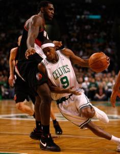 Celtics point guard Rajon Rondo takes the low road as he drives past Trail Blazers center Greg Oden for a first-quarter basket.
