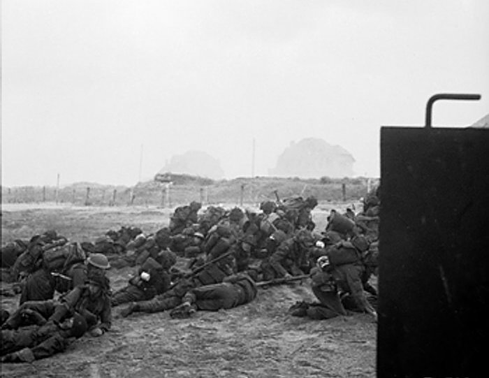British infantry waiting to move off 'Queen White' Beach, SWORD Area, while under enemy fire, on the morning of 6 June.