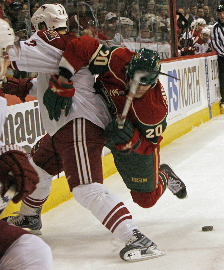 Wild Antti Miettinen (20) and Phoenix James Vandermeer fought for control of the puck.