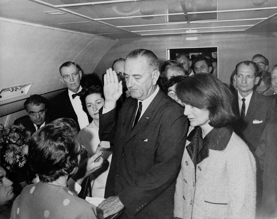 Lyndon B. Johnson being sworn in aboard Air Force One by Federal Judge Sarah T. Hughes, following the assassination of John F. Kennedy.