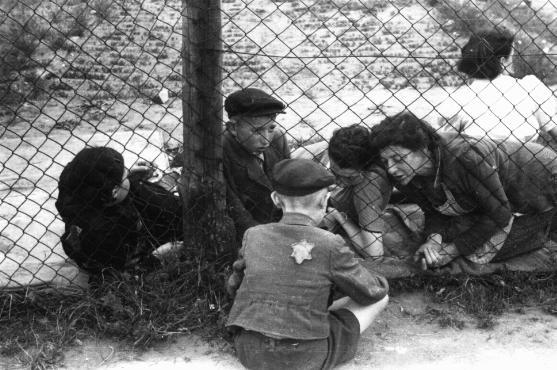 "Family members say goodbye to a child through a fence at the ghetto's central prison where children, the sick, and the elderly were held before deportation to Chelmno during the ""Gehsperre"" action. Lodz, Poland, September 1942."