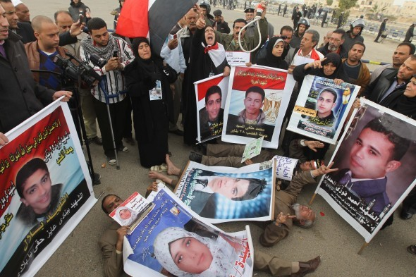 Egyptian protesters hold pictures of people who were killed during the revolution that ousted President Hosni Mubarak during his trial in Cairo on Jan. 5. The chief prosecutor has demanded the death sentence for the fallen dictator.