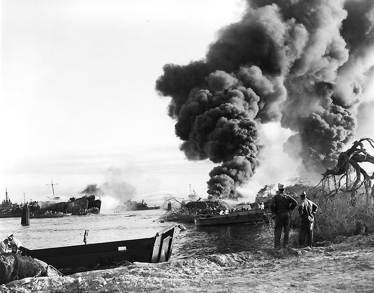 Smoke rises from the wreck of USS LST-480, at right, as tugs and other craft try to put out her fires.