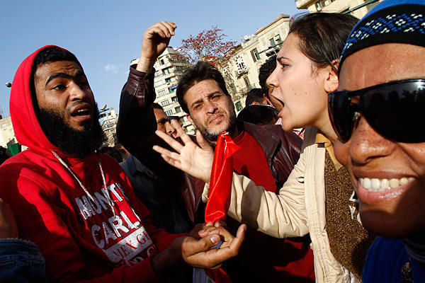 An Egyptian protester argues with a man as hundr