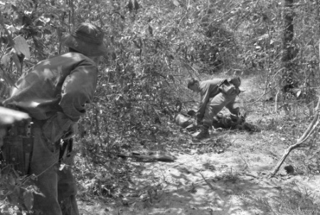 A soldier from 7RAR searching the body of a dead VC following a successful Australian ambush.