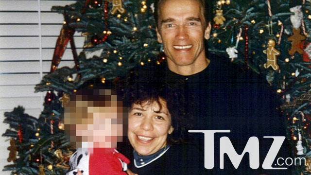 Arnold Schwarzenegger poses for a photo with Mildred Baena and a toddler.