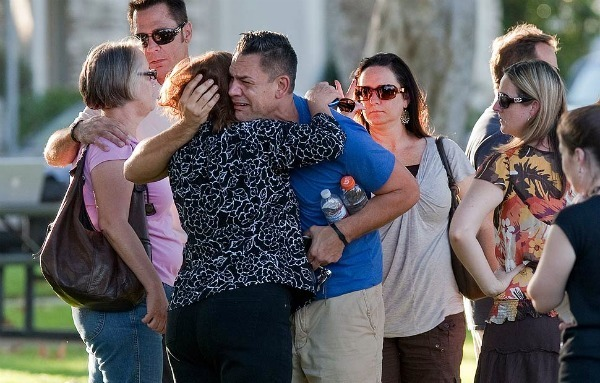 Family members and friends comfort each other outside a community center a block from where eight people were killed when a gunman opened fire at Salon Meritage in Seal Beach.