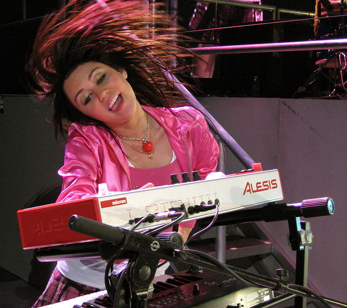 Cyrus playing a keyboard in a concert