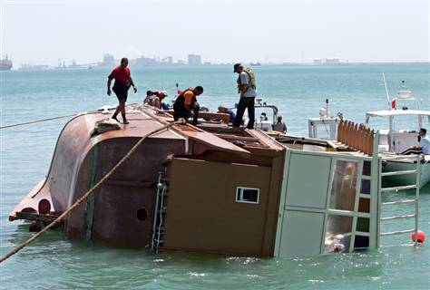 Rescue workers stand on the wreckage of the capsized tourist boat, which was carrying up to 150 people, after bringing it to shore in Bahrain on Friday