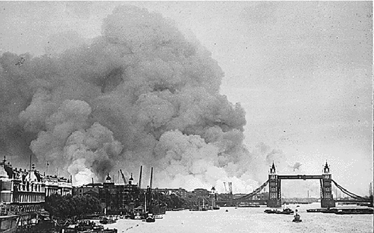 View along the River Thames towards smoke rising from the London docklands after an air raid during the Blitz. 7 September 1940