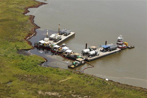 Barges with vacuum trucks are seen along the oil damaged shores in the Northern reaches of Barataria Bay, La., Thursday, June 17, 2010.