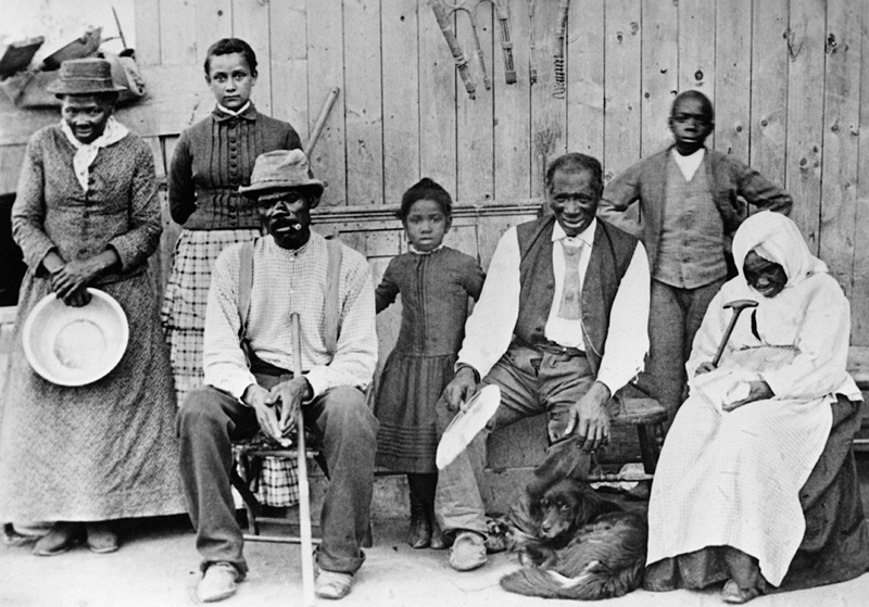 "Left to right:Harriet Tubman; Gertie Davis (adopted daughter of Tubman}; Nelson Davis (husband); Lee Cheney (great-great-niece); ""Pop"" {John} Alexander; Walter Green; Blind Sarah Parker; Dora Stewart (granddaughter of Tubman's brother Robert Ross)"